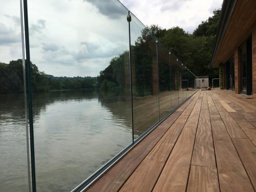 frameless with glass connectors on decking by lake by Balcony Installations